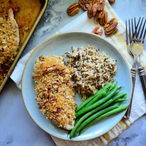 Plated pecan crusted chicken served with green beans and wild rice.