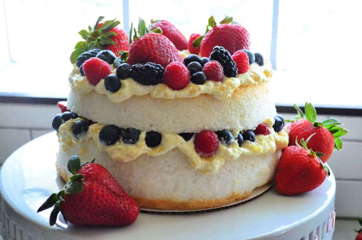 Two layer cake with yellow cream and berries on a white cake stand.