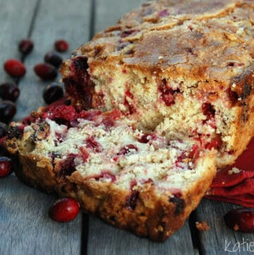 A loaf of Cranberry Bread with a slice cut and loose cranberries around it.