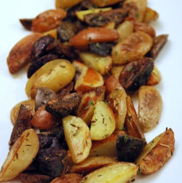 White dish with quartered roasted baby potatoes with herbs.