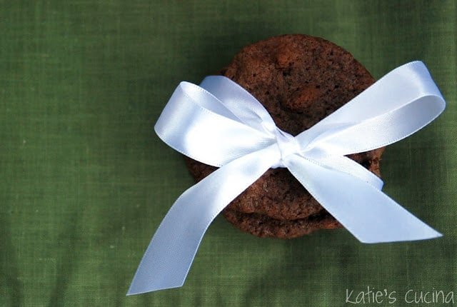 Top view of a white ribbon wrapped around a stack of chocolate cookies on a green background.