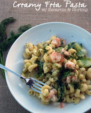 Top view of a white bowl filled with cork screw pasta, greens, and shrimp with text on image for pinterest.