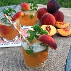 Three glasses of Peach Mojitos on a burlap table cloth.