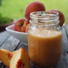 Mason jar of pureed peaches and peaches next to jar.