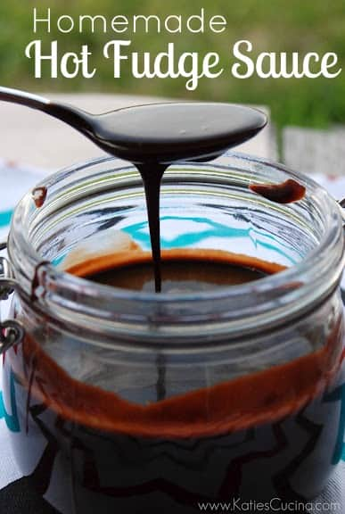 Spoon with chocolate sauce drizzling over jar.