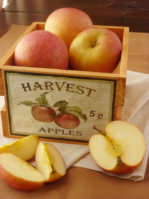 Basked of apples with an apple cut in half and in wedges in front of the basket.