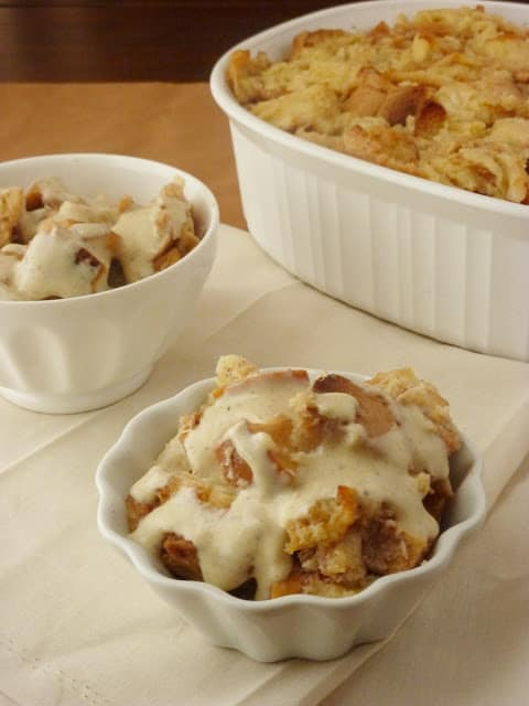 Two bowls filled with bread pudding with sauce .