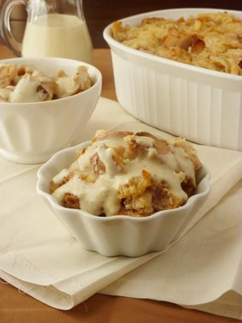 Two white bowls on a cream colored cloth filled with bread pudding and cream sauce.