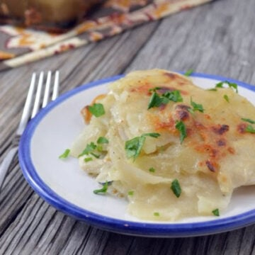 Thinly slided potato gratin with slightly browned top garnished with herbs on a plate.