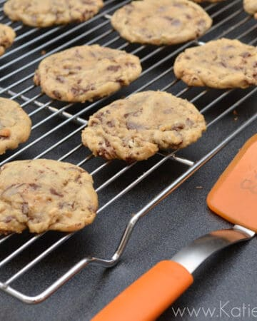 Cookies on a wire cooling rack with a orange spatula next to it.