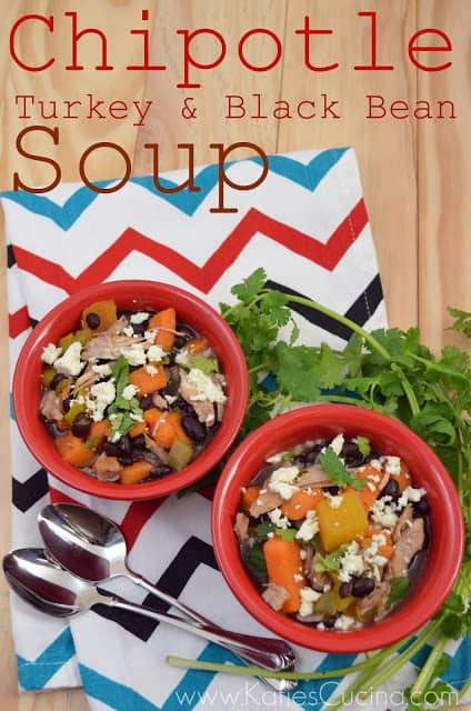 Top view of two red bowls filled with turkey, black beans, and vegetable soup with text on image for Pinterest.