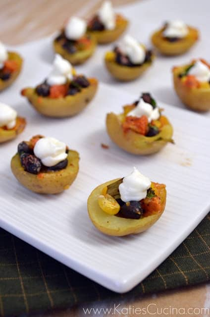 White platter with a dozen mini potatoes with corn, black beans, and sour cream.