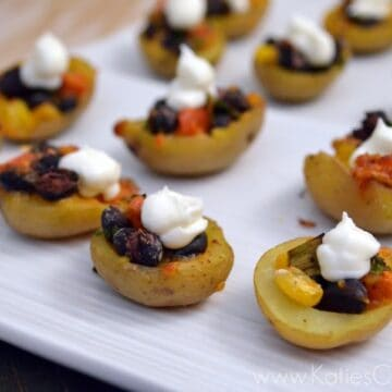Mini potato skins on a white plate filled with corn, black beans, and sour cream.