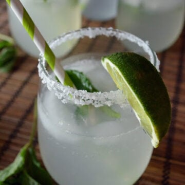 stemless wine glass with salted rim with lime wedge containing tranluscent whiteish beverage and.