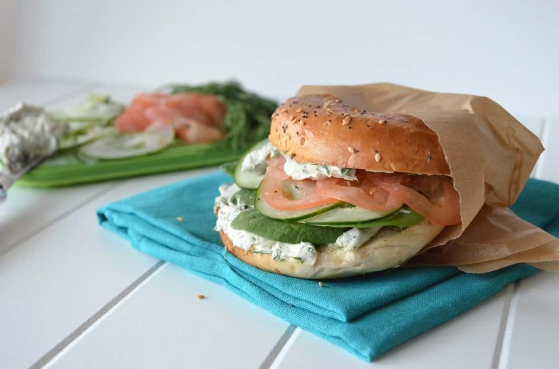 Side view of everthing bagel sandwich with garlic-herb cream cheese, tomato, cucumber, and spinach.