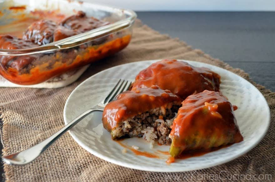 Plated meat-stuffed cabbage with red sauce glaze and fork on side.