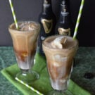 two sunday glasses containing brown creamy liquid with chunks of ice cream and paper straws with guinness bottles in background..