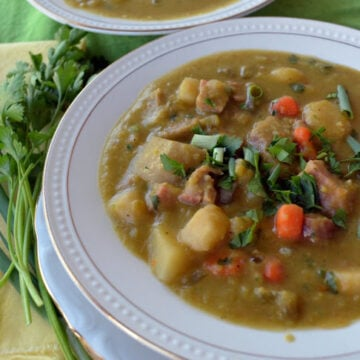 Two bowls of split pea soup with carrot sliches, potato chunks, and parsley garnish visible.