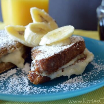 Plated French Toast topped with powdered sugar and banana slices.
