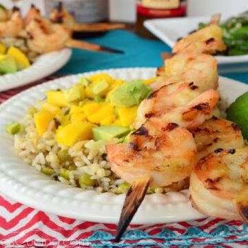 Grilled shrimp skewers plated over bed of roasted mango chipotle rice with lime slice on tablecloth.