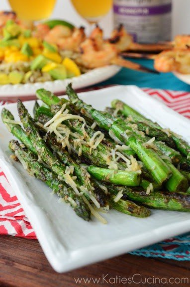 Plated Grilled Asparagus topped with parmesan. Grilled shrimp skewers in background.