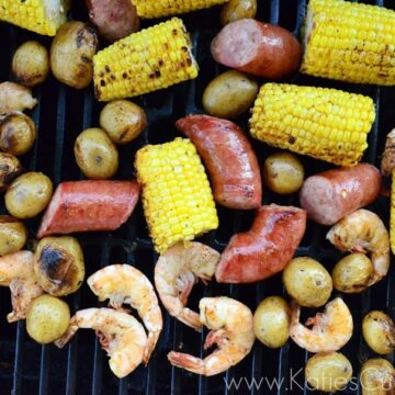top view of grilled corn, punch potatoes, sausage, and shrimp on the grill.