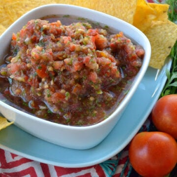 Bowl of Chunky Chipotle Cherry Tomato Salsa served with corn tortilla chips on the side.