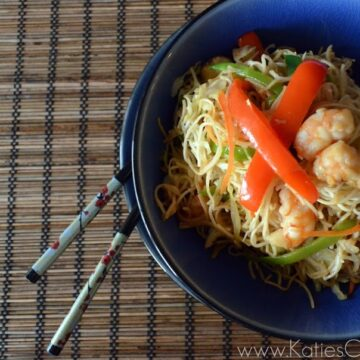 Bowl of Shrimp Veggie Lo Mein with chopsticks sticking out on bamboo placemat.