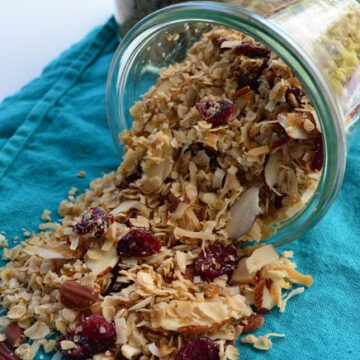 glass intentionally tipped to show spilled contents of Coconut Cherry Granola over blue tablecloth.