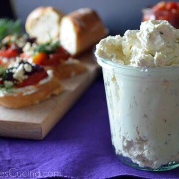 Glass containing Garlic and Herb Whipped Feta with board of Greek Crostinis in background.