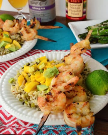 Grilled Shrimp Skewers plated on bed of wild rice with mangos.