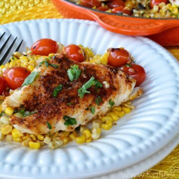 Browned fish topped with cilantro and cherry tomatoes on bed of fresh mexican corn salad.