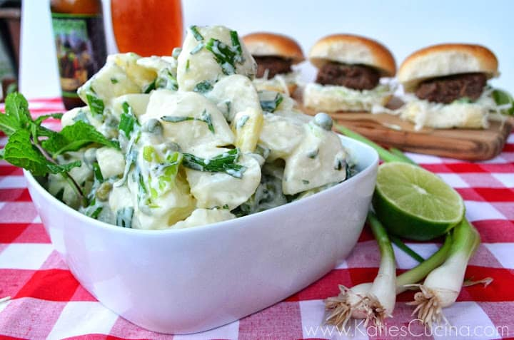 Bowl of Green Onion & Pea Potato Salad next to green onions and limes with sliders in background.