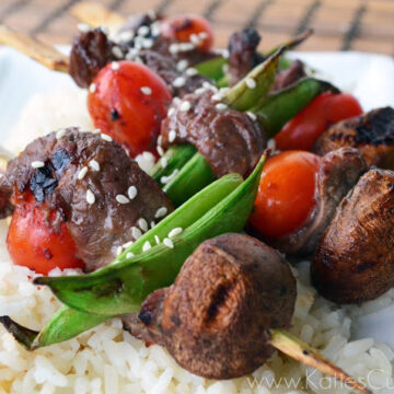 skewers of snow peas, beef, mushrooms, cherry tomatoes garnished with sesame seeds over white rice bed.