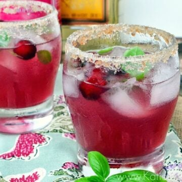Two sugar rimmed glasses filled with ice, cranberries, basil, and pink liquid.