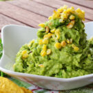 Guacamole in a bowl topped with grilled corn decoratively placed by cilantro.