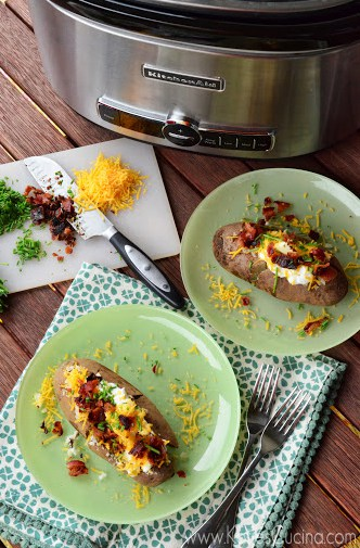 Top view of loaded baked potatoes on green plates with the slow cooker at the top of the photo.