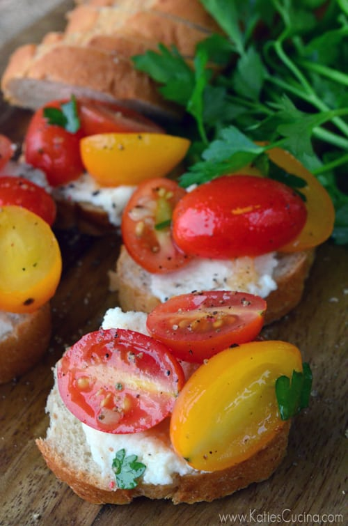 Four slices of baguette topped with ricotta and grape tomatoes.