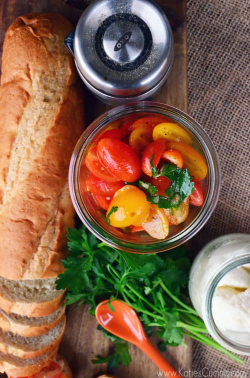Top view of a jar of sliced grape tomatoes with baguette next to it.