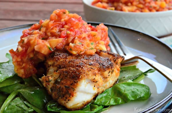 White circle plate with a bed of spinach and blackened fish on top with salsa.