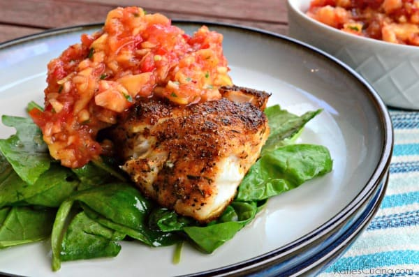 Blackened white fish topped with peach salsa resting on a bed of spinach on a white plate.