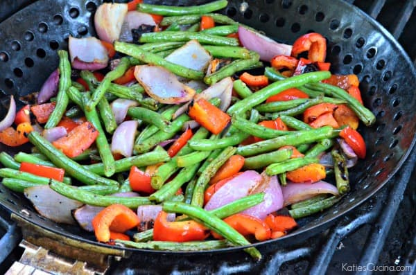 Black grill with a grill basket filled with grilled green beans, red bell peppers, and red onions.