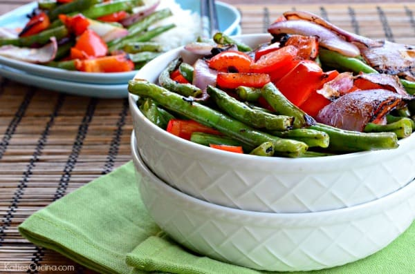 Two white bowls stacked filled with grilled green beans, red bell pepper, and red onions.