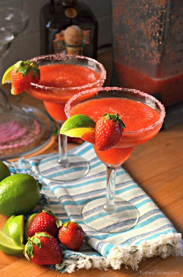 2 Frozen Strawberry Margaritas with sugar and a blender and sugar in the background.