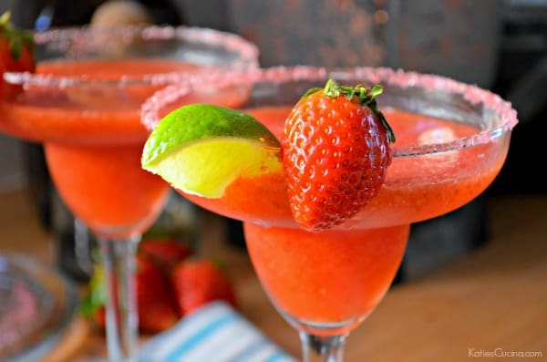 Close up of a horizontal photo of two Frozen Strawberry Margaritas with limes and strawberry garnish.