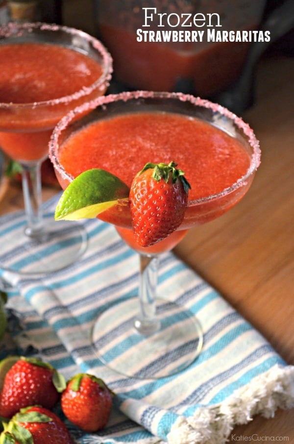 Two frozen strawberry margaritas on a blue striped cloth with text on image for Pinterest.