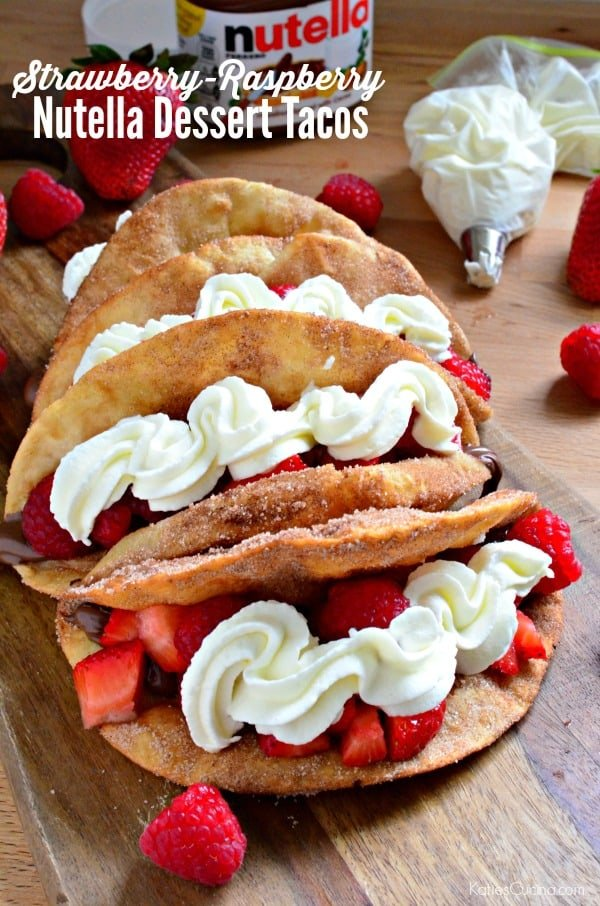 Dessert tacos filled with strawberries and whipped cream on a wood board with text on image for Pinterest.