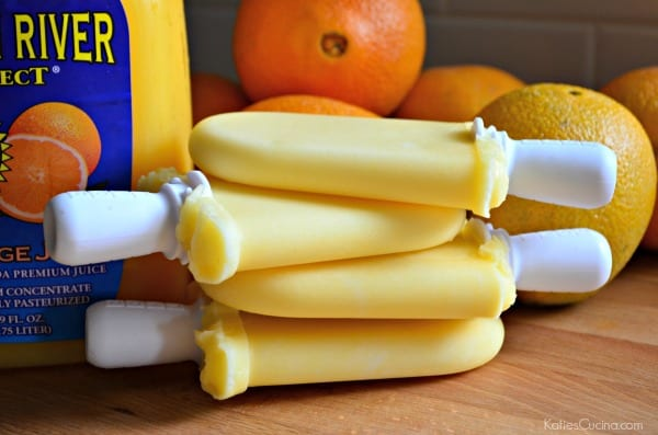 Four stacked orange popsicles with orange juice and oranges in the background.