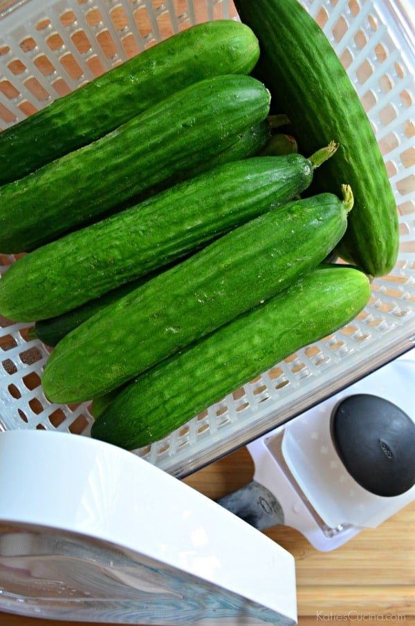 Top view of a white basket filled with whole mini cucumbers on a wooden cutting board.