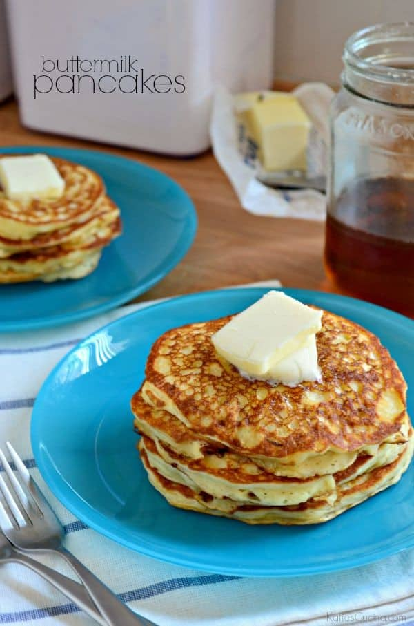 A stack of buttermilk pancakes with a square of butter on top with syrup in the background.